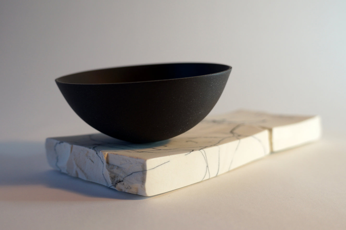 Black rocking bowl on split inlaid plinth
