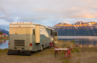 RV with portable water storage at lake during sunset