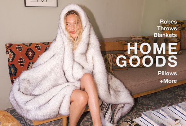 Woman on couch wrapped in faux fur blanket throw