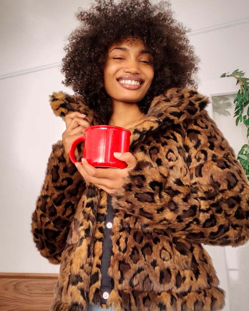 Woman wearing faux fur coat holding cup