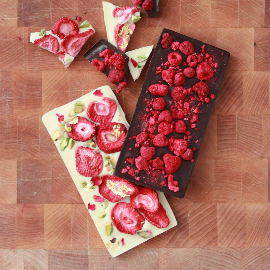 Intense 70% Dark Chocolate Raspberry Bar Intensely cocoa-forward 70% Cacao Barry dark chocolate sourced from West Africa studded with raspberries for a balance of slightly bitter and bright tartness.  Lux White Chocolate Bar Creamy, silky, Belgian white chocolate balanced with slightly tart strawberries, lightly salted and roasted pistachios, crushed rose petals, and adorned with brilliant 24k gold leaf.