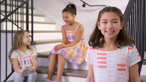 Three young girls wearing spring clothing.
