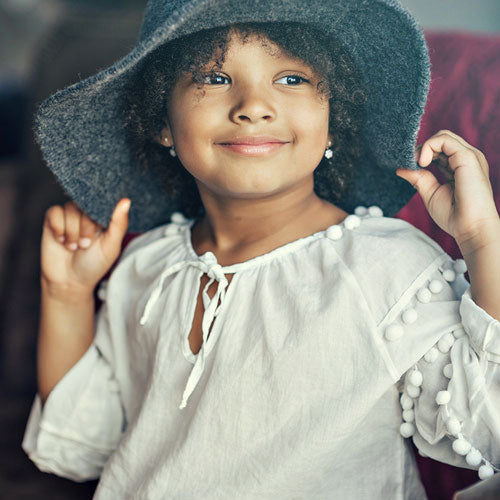 Young girl smiling while holding the brim of her grey hat, wearing a white shirt.