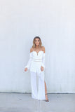 The Aura Jumpsuit is a gorgeous white off shoulder jumpsuit.  The lightweight chiffon  jumpsuit has a sweetheart neck line, is partially lined, an has back zip closure.