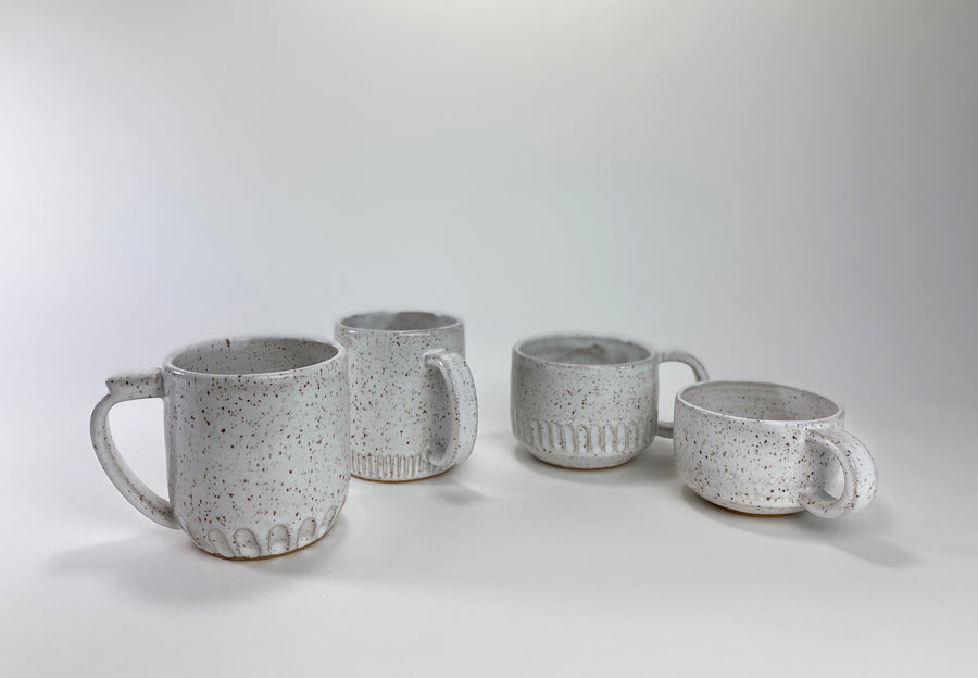 Assorted Family of Carved White Stoneware Ceramic Mugs