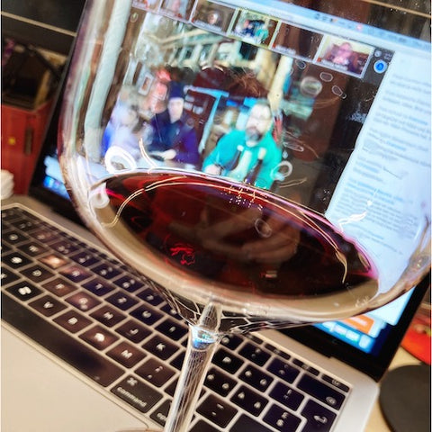 different perspective of wine through online wine events, glass with red wine, screen with online wine tasting in background