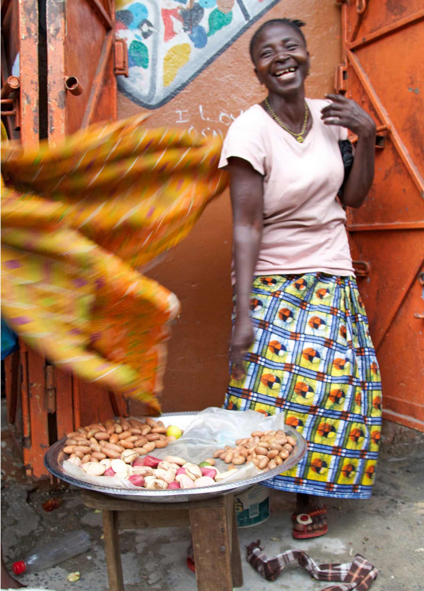 African woman in Sierra Leone dancing next to cola nuts