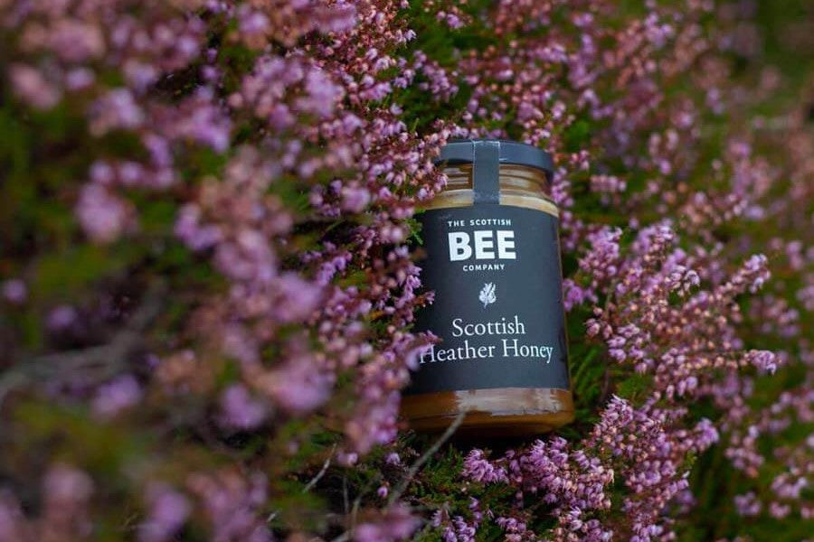 A jar of Scottish Heather Honey in a heather moor