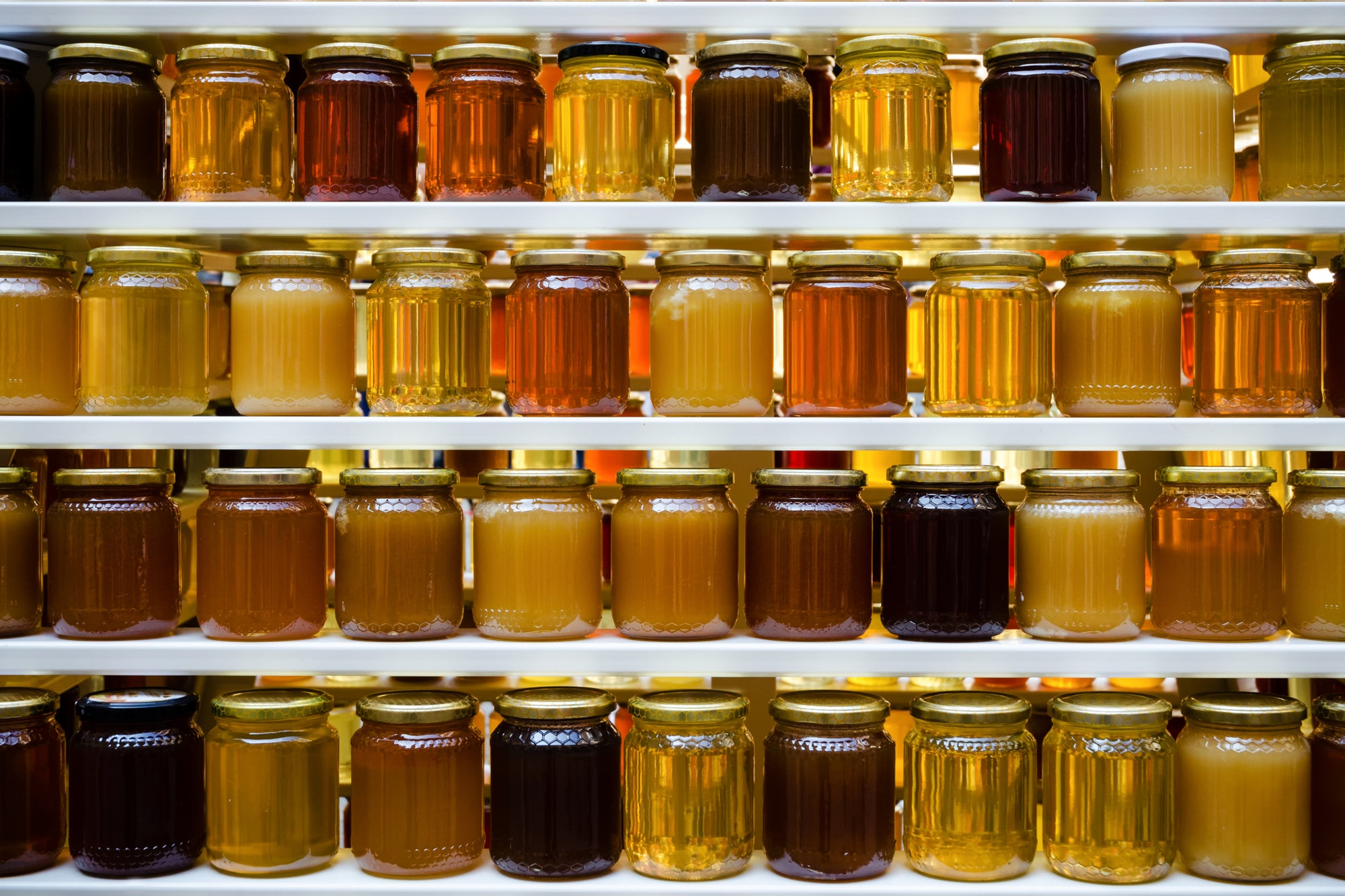Jars of crystallised and runny honey on shelves