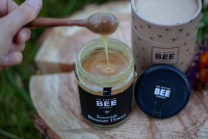 Hand drizzling Scottish Bee Company Honey into a jar