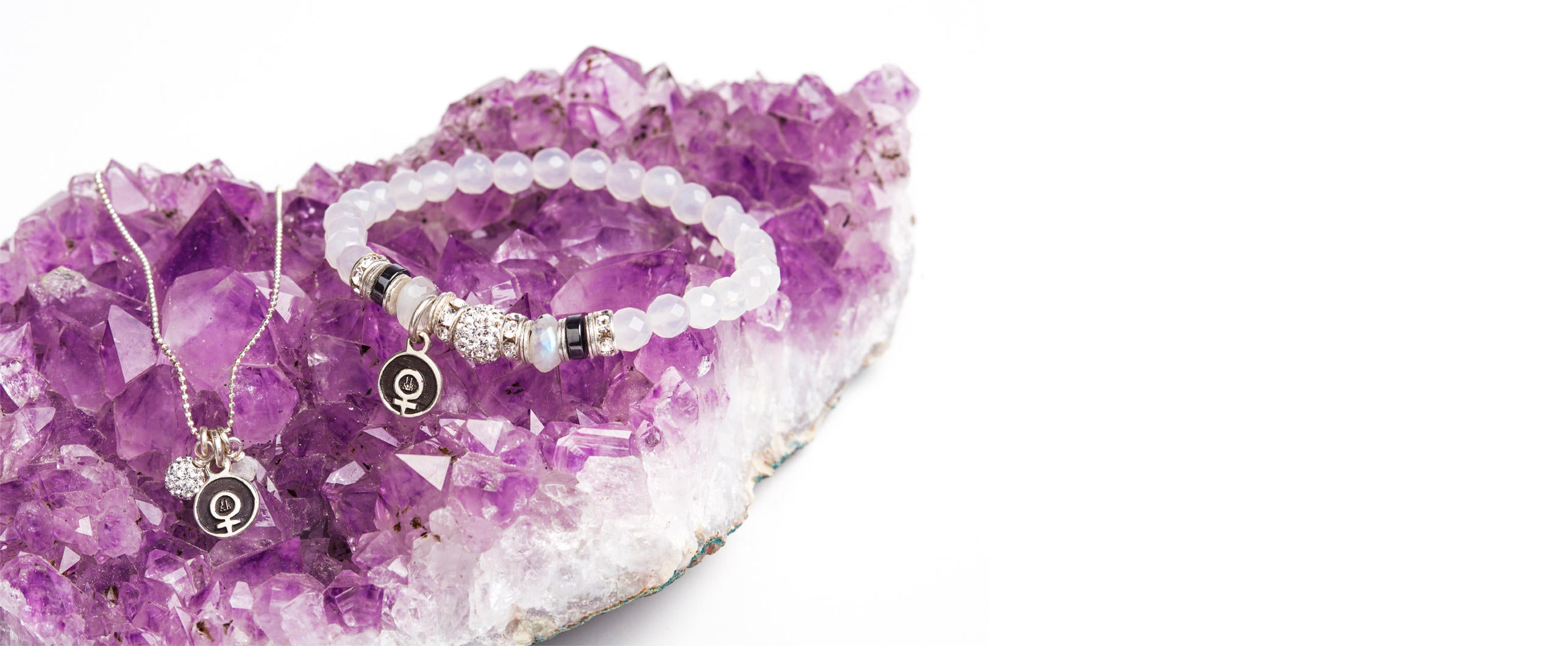 Venus necklace and bracelet laying on an amethyst gemstone