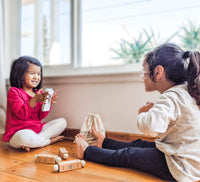 2 girls playing with Little Bud Kids Spin-and-Read Phonetic Blocks, a CVC Phonics Tool
