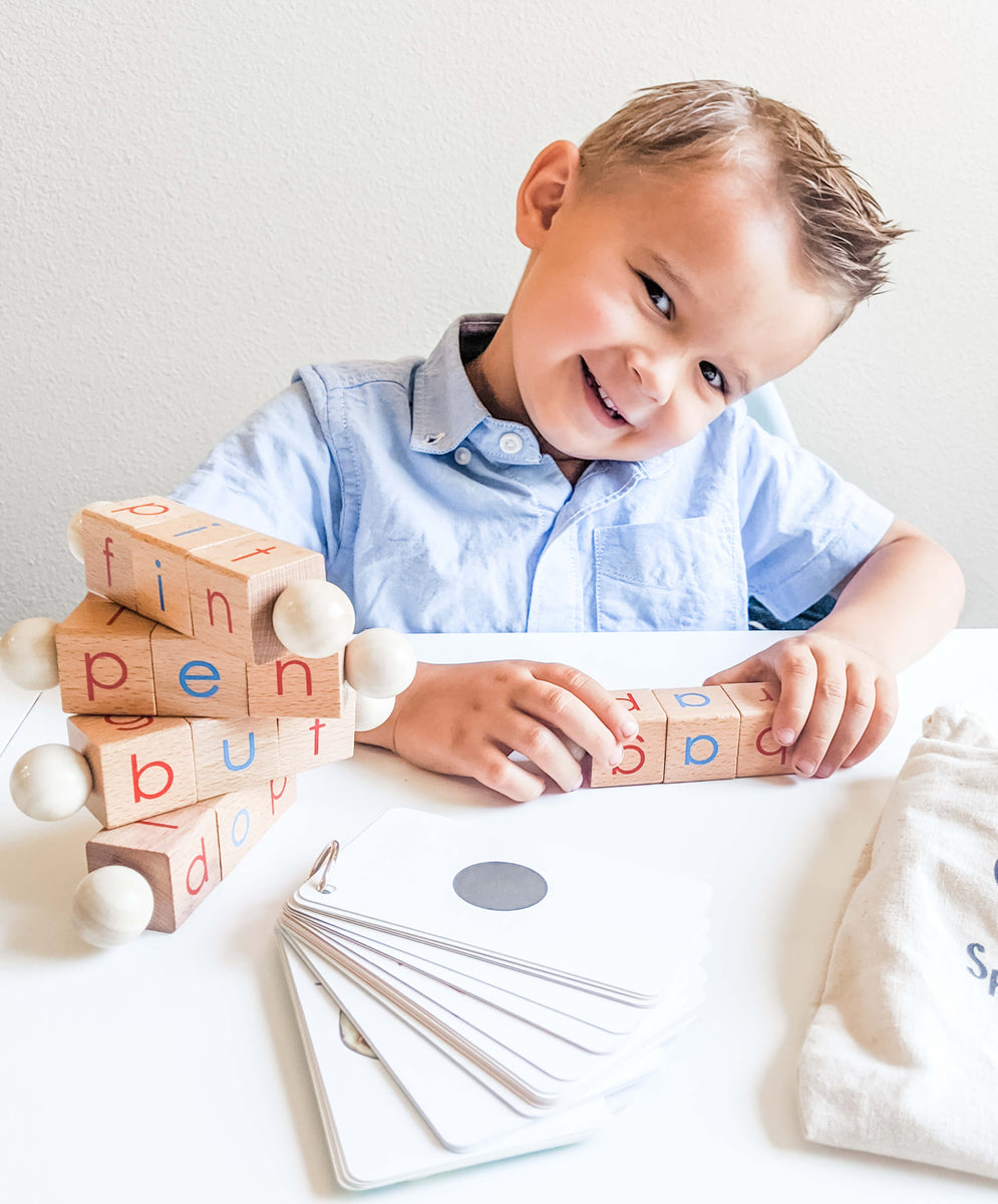 Boy using his Montessori-inspired reading blocks to learn to read