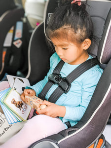 Girl playing with Spin-and-Read Phonetic Reading Blocks in the car