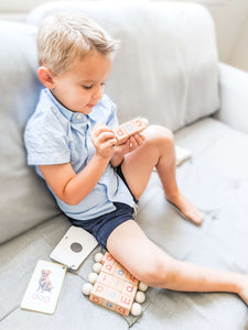 Boy playing with Little Bud Kids Spin-and-Read Blocks on couch