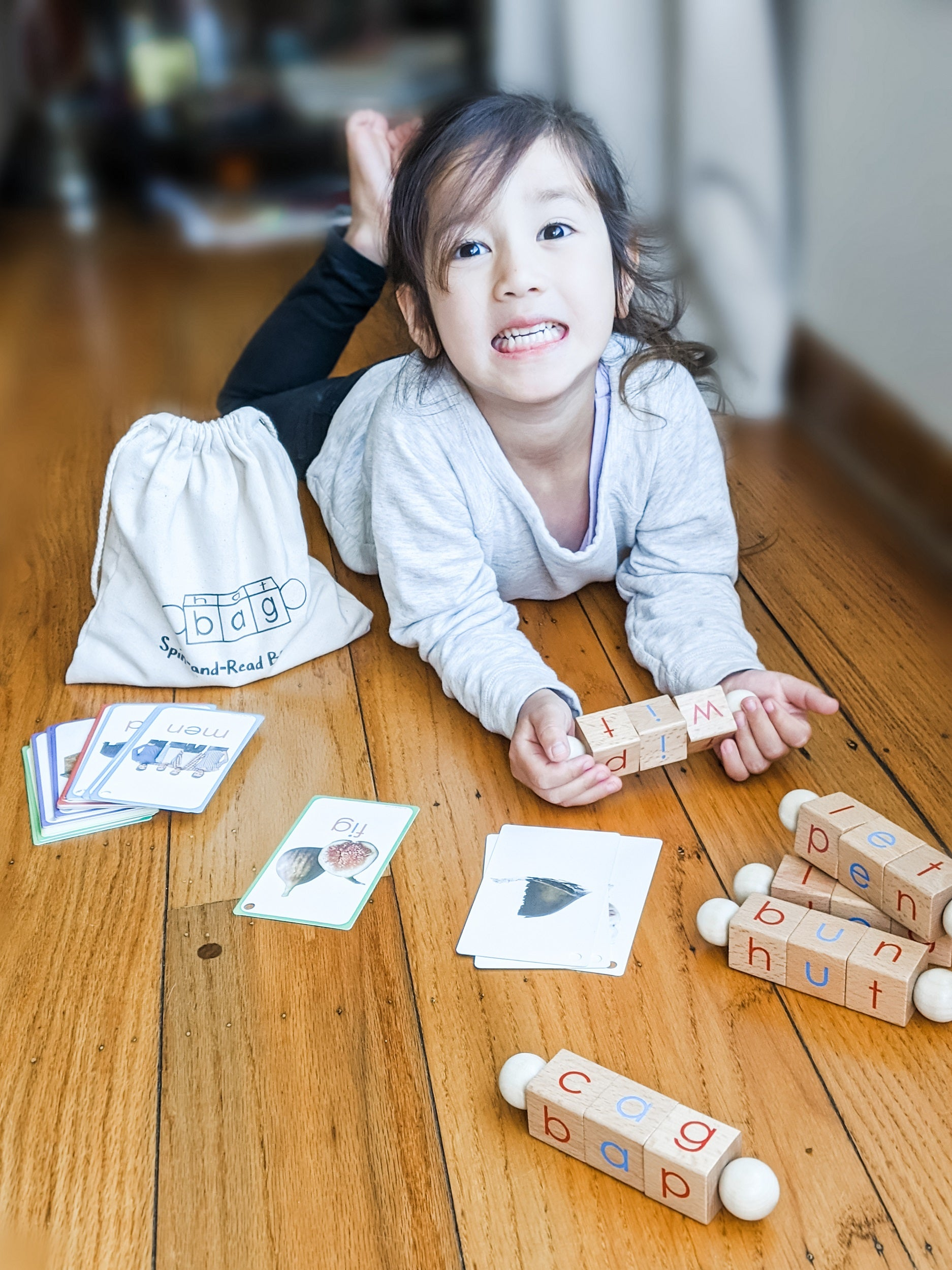 Girl playing with CVC flashcards & reading blocks