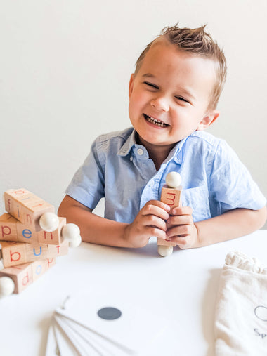 Caucasian boy boy learning to read using Spin-and-Read Blocks