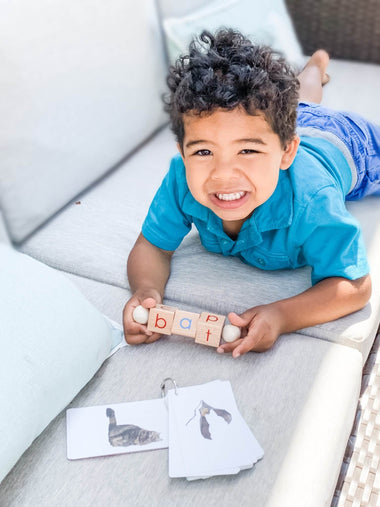 Boy playing with his phonetic reading blocks, a Montessori language toy