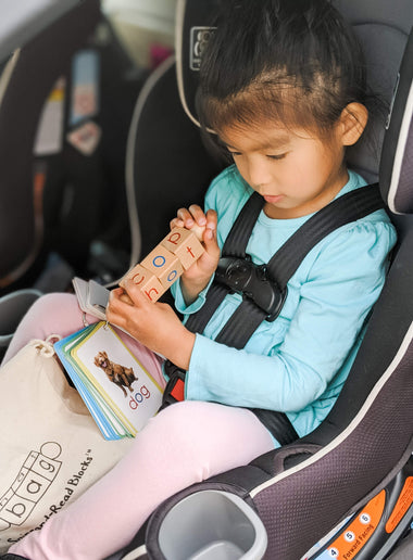 girl learning how to rea while in the car
