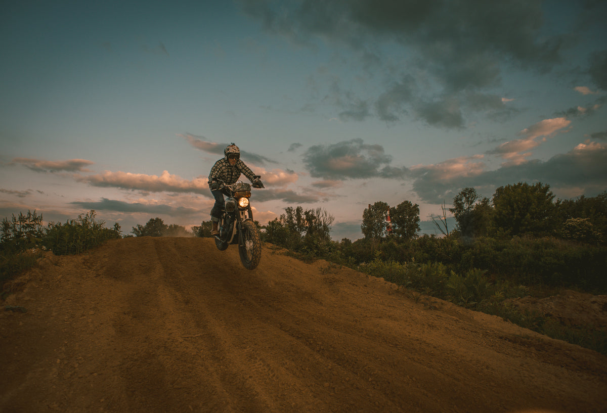 Man jumping on dirt track in Crave for Ride motorcycle shirt, open helmet goggles and motorcycle jeans