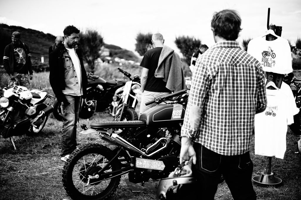 Men wearing motorcycle clothing watching Crave for Ride T-shirts and custom motorcycles