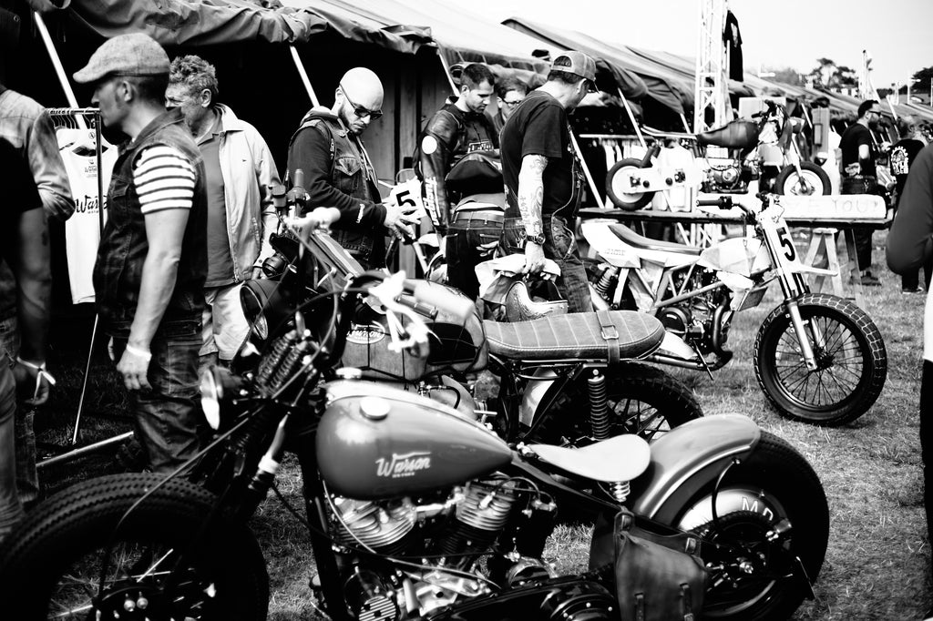 Stylish motorcyclists watch custom motorcycles at tents at Wheels and Waves village