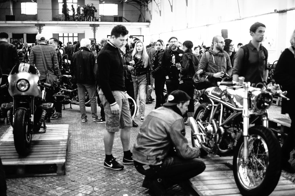 Crowd watching custom motorcycles at Wheels and Waves Festival 2015 dressed in motorcycle jackets and snapbacks, drinking beer