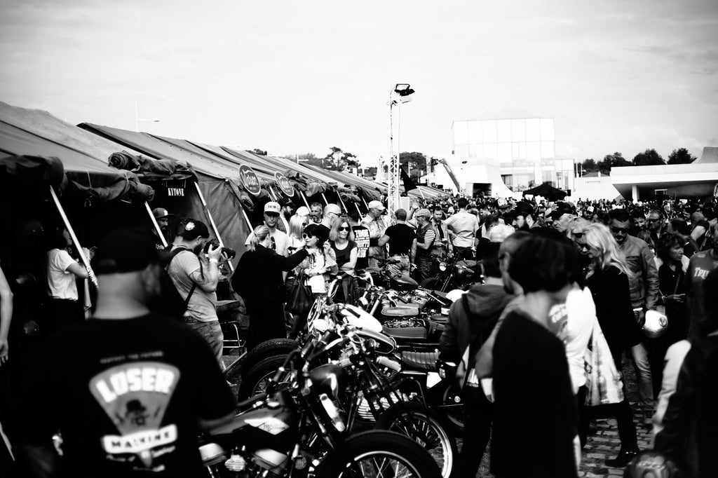 Crowd watching custom motorcycles taking photos chatting at Wheels and Waves Festival 2015