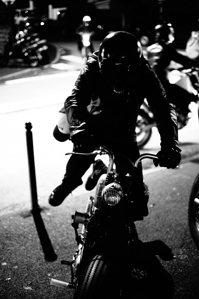 A motorcyclist is starting his motorcycle wearing leather motorcycle jacket has snapback hat attached to his motorcycle trousers