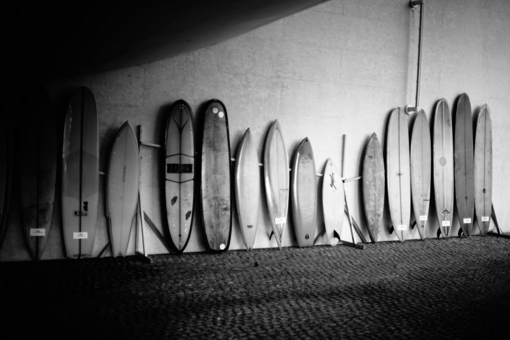 15 different surfboards leaning against a wall at Wheels and Waves Festival