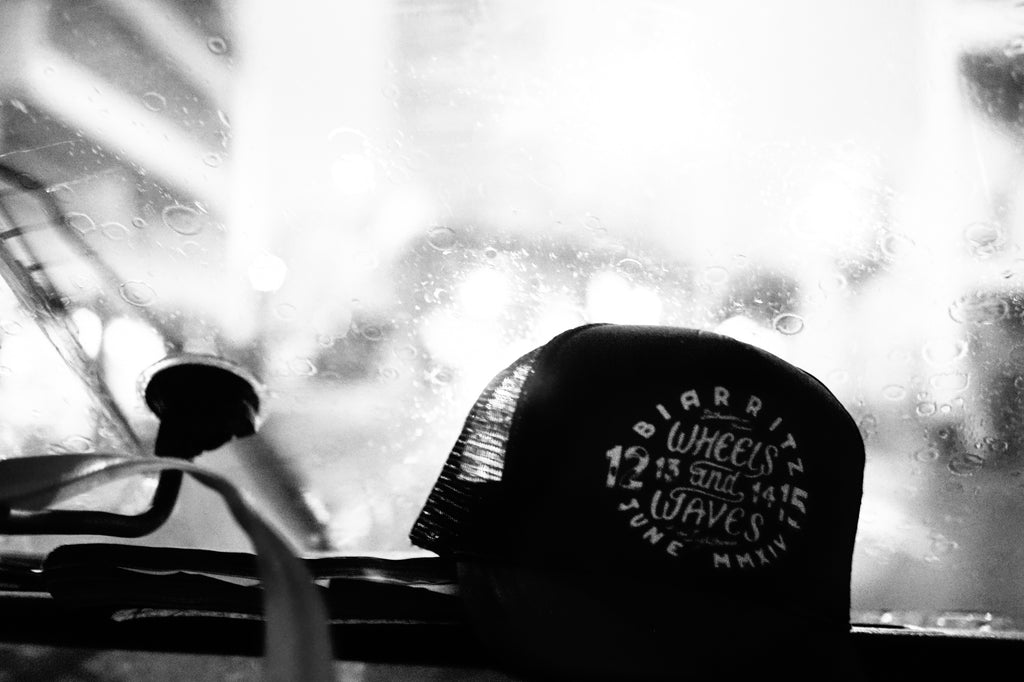 Wheels and Waves snapback hat on a rainy windshield of an old VW van