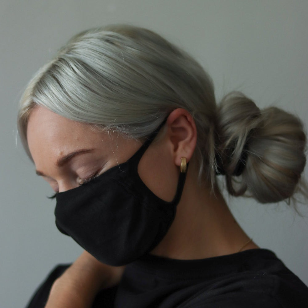 Woman wearing black reusable standard mask