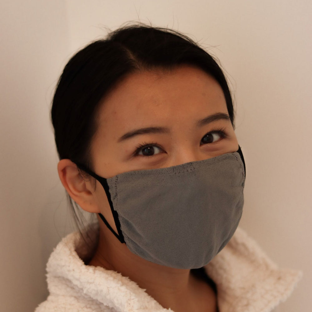 Woman wearing grey triple-layer reusable mask