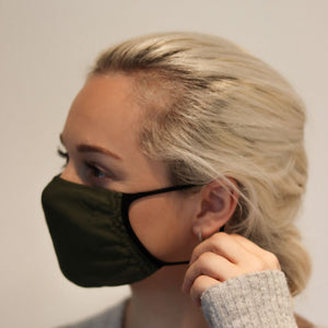 Woman wearing olive triple-layer reusable standard mask