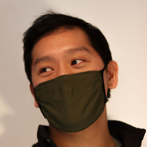Man wearing olive green triple-layer reusable mask