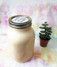 "Load image into Gallery viewer, mason jar of white liquid ""hippie mylk"" beside a potted plant with colorful tie dye backdrop"