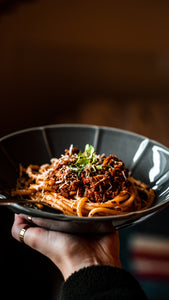 Bowl of pasta mixed with bolognese sauce with shredded cheese and herbs on top