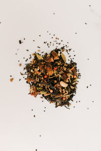 small pile of dried tea mix on white surface