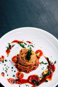 large white plate with noodles and spaghetti sauce, halved tomatos and herbs on top