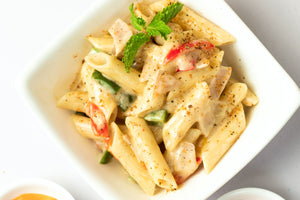 white plate with penne noodles covered in white alfredo sauce