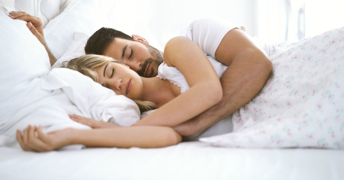 Man and woman sleeping comfortably together in a bed