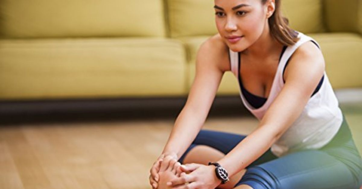 A woman stretching and wearing a fitness tracker watch on her wrist while sitting on a yoga mat.