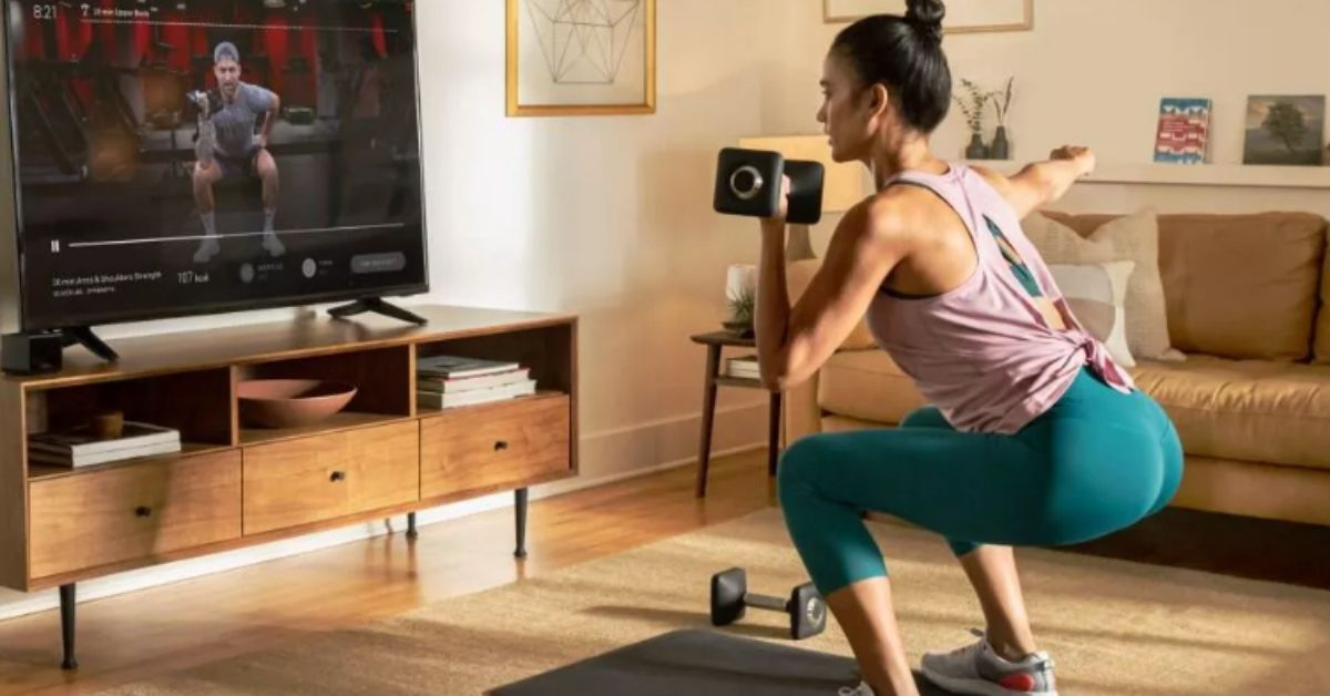 A woman exercising in front of her TV while watching a workout video streaming.