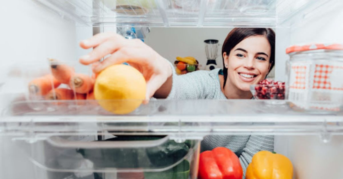 A woman looking inside the refrigerator and reaching for a lemon.