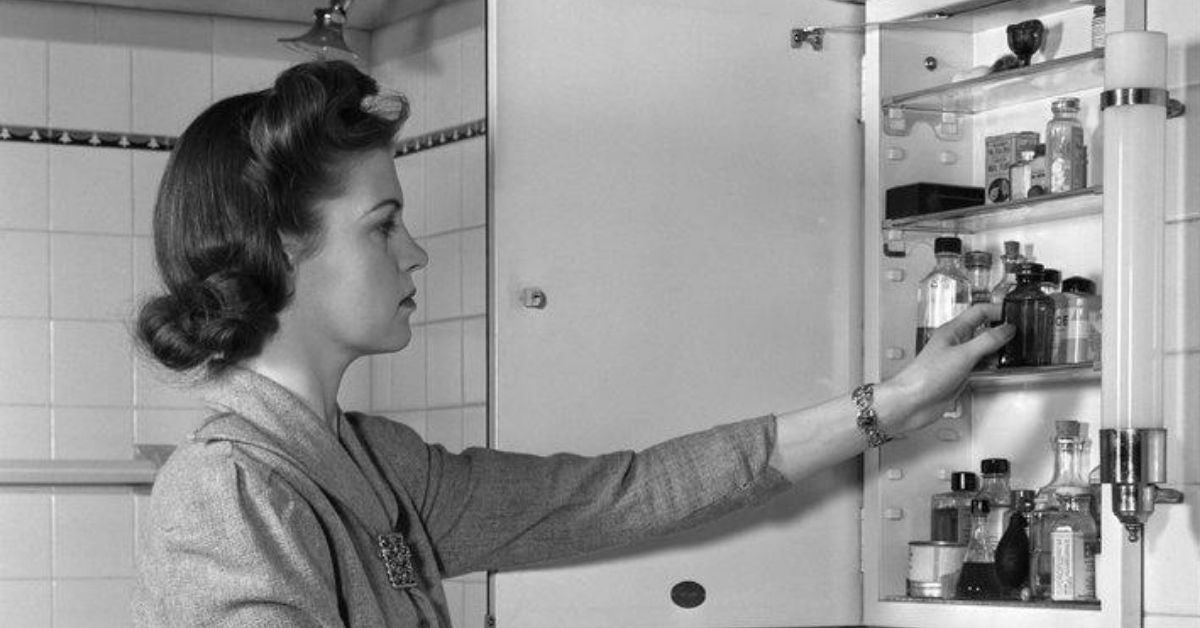 B&W photo of a woman at a medicine cabinet