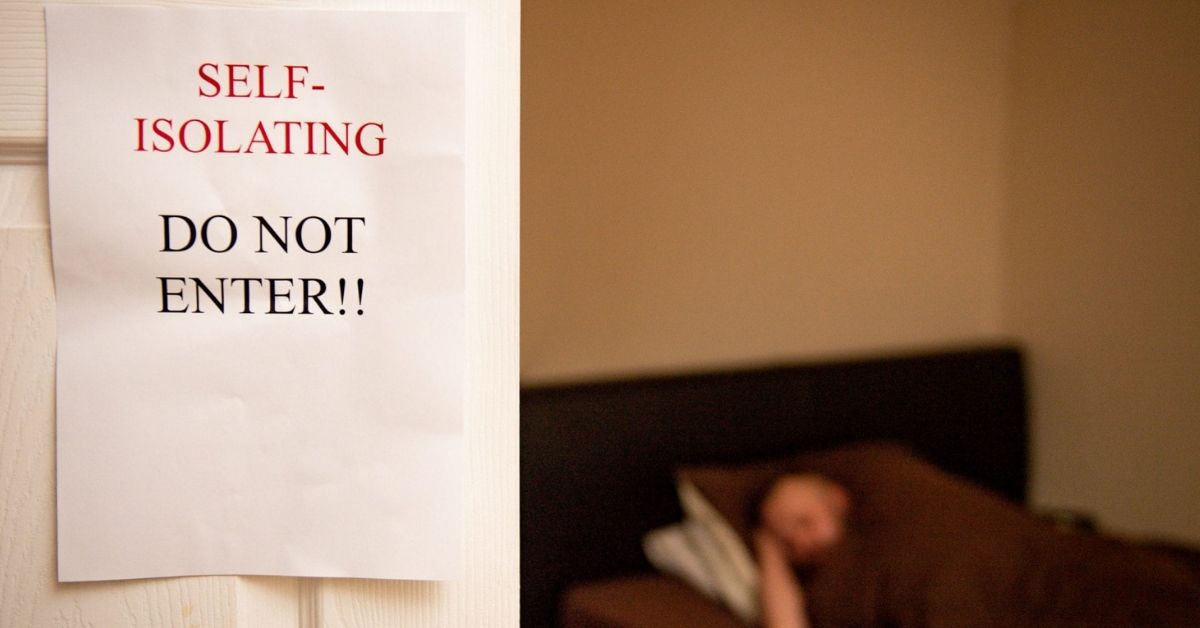A sign on the door reads Do Not Enter, Self Isolating. There is a person sleeping in the background.