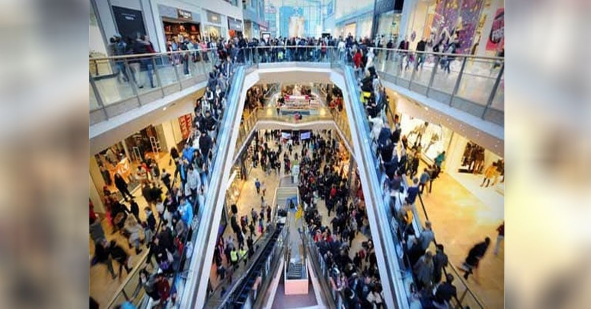 A busy shopping mall with many people and escalators.