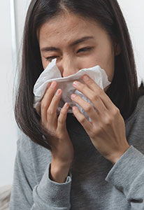 Woman with allergic Rhinitis Blowing nose