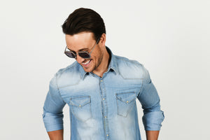 man wearing sunglasses and looking down and smiling wearing denim shirt