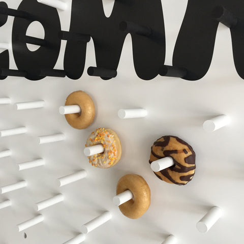 White pegboard for donuts with bespoke black lettering and white pegs